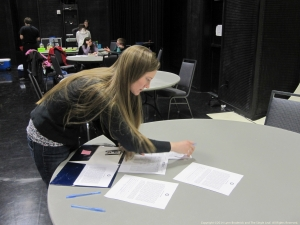 Gina, a production assistant, is busy backstage making sure all the paperwork is in order.